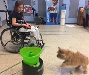 Geneviève passe un merveilleux moment à appuyer sur le bouton sur ses genoux pour envoyer des balles voler pour le petit chien.