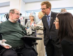 CanAssist client Gordon Jones chats with ministers Lake and Stilwell about his Zero-Gravity Arm Support.