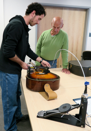 CanAssist's Mike Lewis readies the Guitar Strummer for Charles.