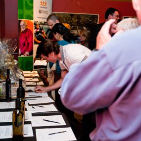 People bid on 100 Kilometres of Wine, a slient auction.