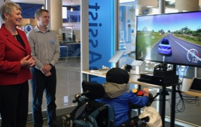 Minister Conroy and a CanAssist staff member watch a visiting child try out the Accessible Gaming Controller.