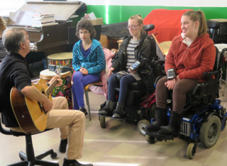 Music therapist Allan Slade on guitar and (left to right) Kaitlin, Corrine and Sierra. Corrine and Sierra play instruments using the iPods attached to their arms, while Katlin presses a grey accessibility switch.
