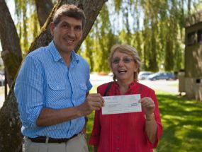 CanAssist's Nigel Livingston accepts the cheque from Maureen Duncan, a member of the Telus Victoria Community Board.