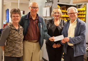 Dola Dube and Tom Pringle of the Norgaard Foundation (both left) present a cheque to Robin Syme and Howard Brunt of CanAssist.