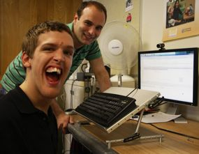 Dan (left), who types with his mouth, tries out his new Keyboard Support Stand, which was built by Mike .