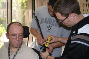 Roger (seated) gets help from co-op student Alex (middle) and CanAssist's Brandon.
