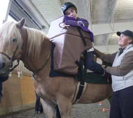 On delivery day, Whitney is excited to finally be able to sit upright and see where she's going while riding Danny. Whitney's instructor, Stella (shown right), stands nearby at all times.