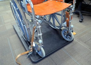Safety straps keep the wheelchair securely in place.