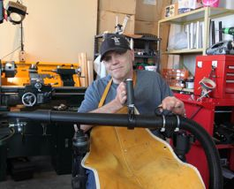 Gerry holds the wand of the Adapted Shop Vac: he grips the customized handle with his right hand and the smaller brace with his right