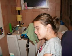 Grace washes her own face at home using the clamp's washcloth attachment.
