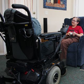 Shelley sits in her favourite easy chair and guides her power chair to her.