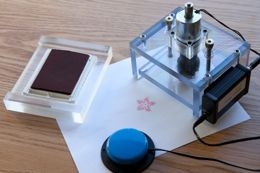 The stamper (right), shown with stamp pad. Pressing the blue accessibility switch activates the stamper.